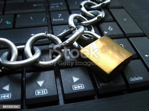 Chain with lock on computer keyboard. It means block chain technology using or laptop banned or internet banned. Symbol of computer addiction, games, social networks, block chain for crypto currency and so on