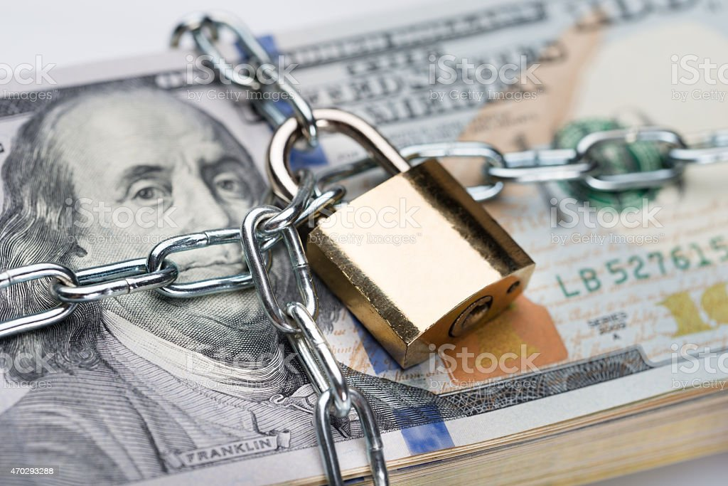 Chain And Padlock Around Dollar Bundle Closeup of metallic chain and padlock around dollar bundle 2015 Stock Photo