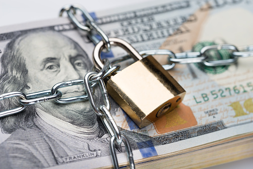 Chain And Padlock Around Dollar Bundle Stock Photo - Download Image Now