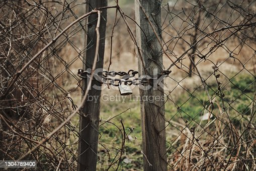 istock Chain and padlock on an old wooden fence. 1304789400