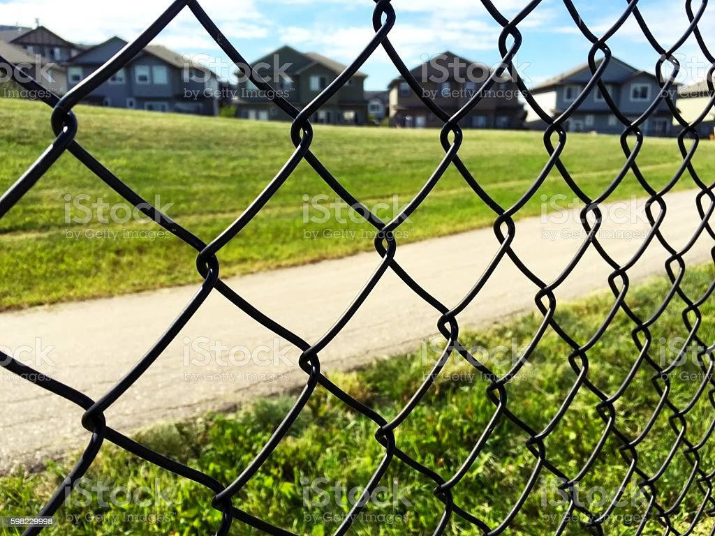 chain fence on green grass, houses and sky background foto royalty-free
