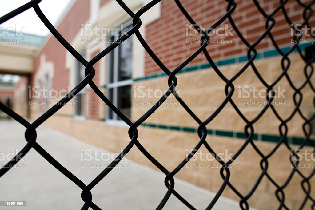 Chain link fence and school building. Education. Nobody. stock photo