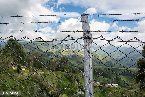 Chain link fence with rural landscape in the background in Salento, Colombia