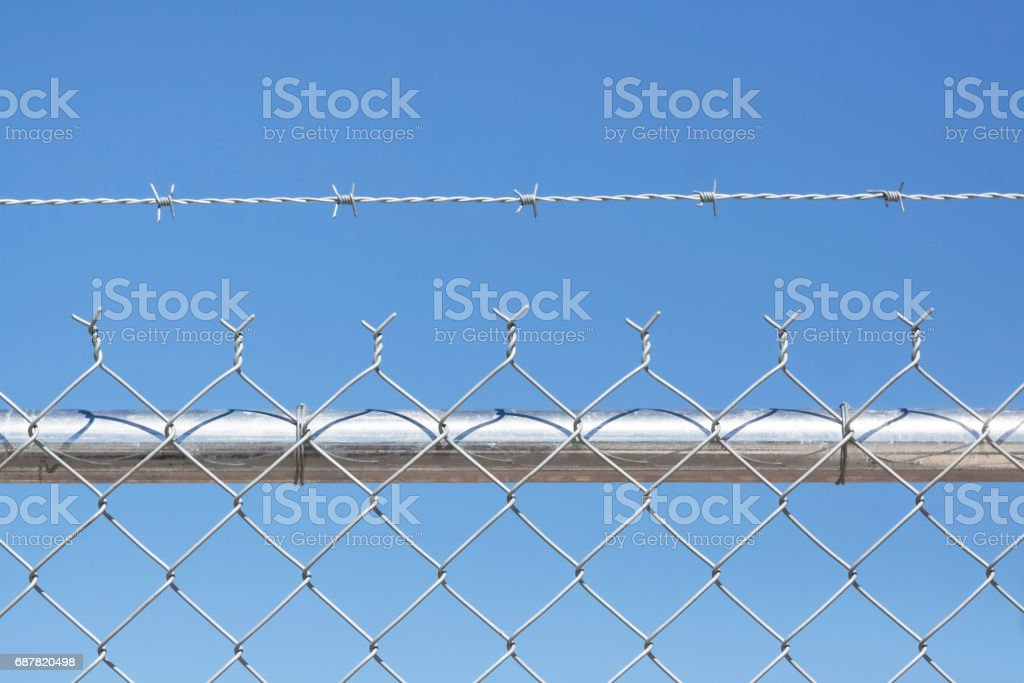 Chain link fence with barbed wire, blue background, copy space stock photo