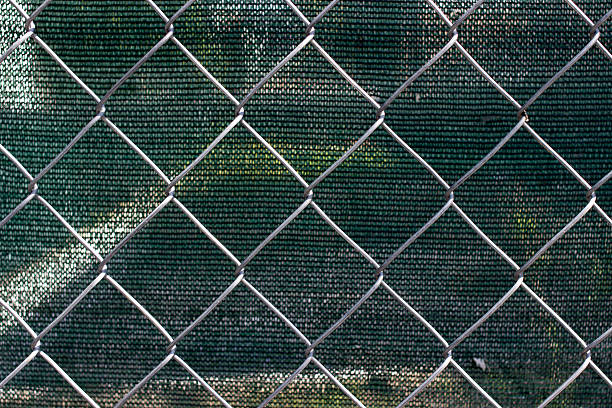 Chain link fence with fabric screen Chain link fence with green fabric screen kathrynsk stock pictures, royalty-free photos & images