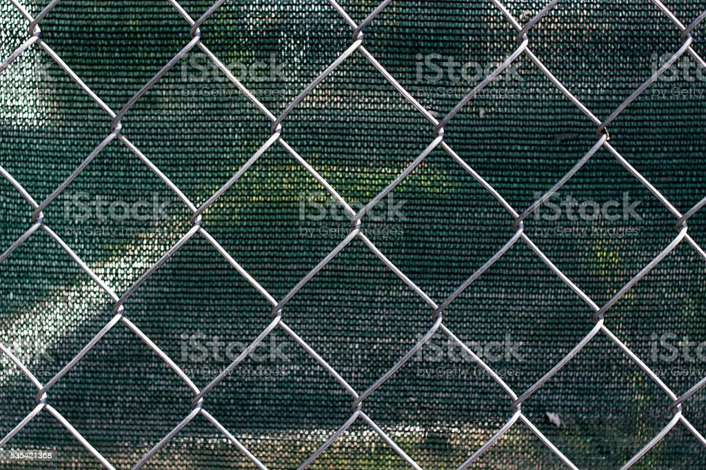 Chain link fence with fabric screen stock photo