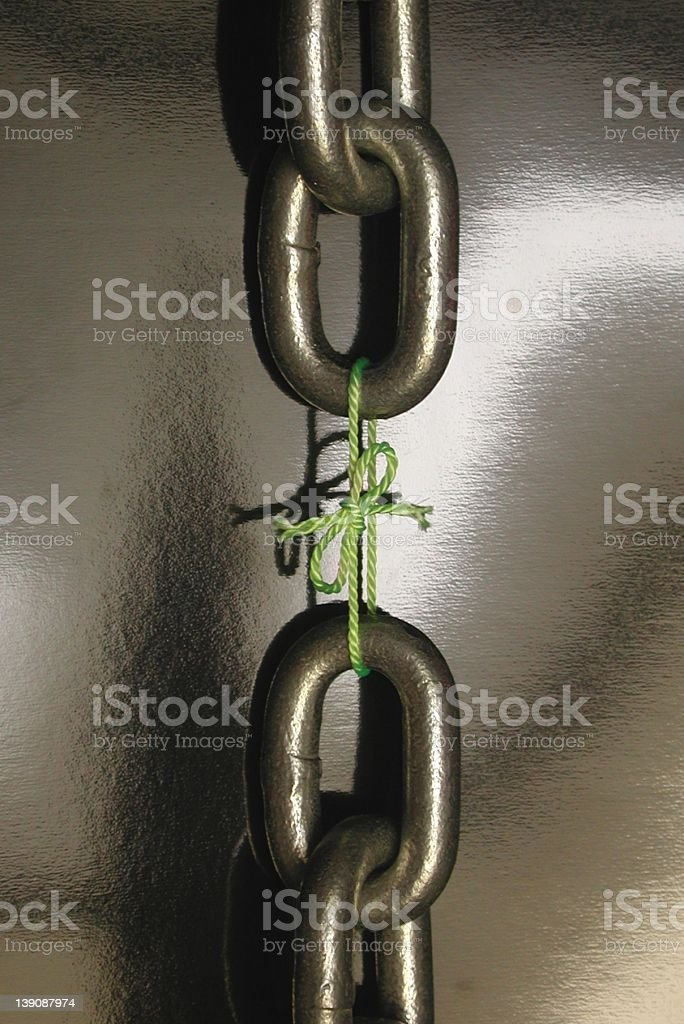 Chain links tied together with string stock photo