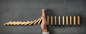 istock Chain Reaction In Business Concept, Businessman Intervening Dominoes Toppling 1126856471
