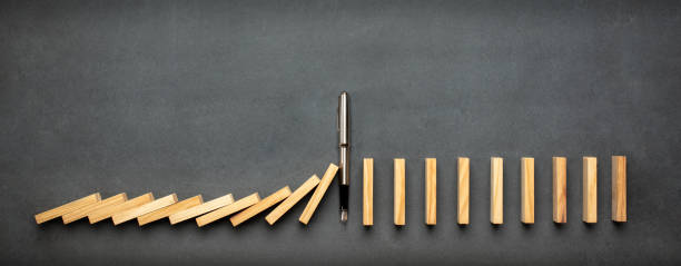 Chain Reaction In Business Concept, Pen Intervening Dominoes Toppling stock photo