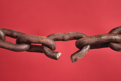 Old rusty Chain with broken or weak link on red background. Concept of weakest link or breaking binding chains