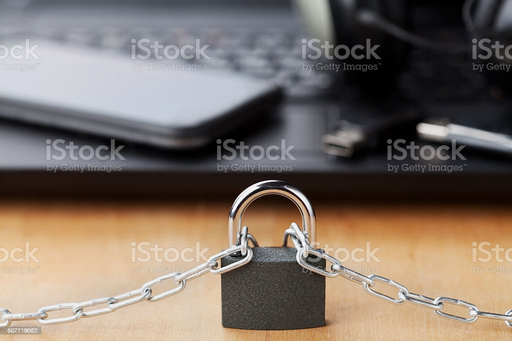Chain with lock in front of the laptop and smartphone stock photo