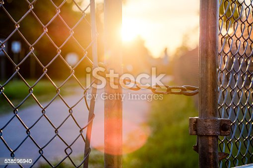 An old fence gate slightly ajar, revealing a path towards the sunlight. This gate was found at an old and abandoned school.