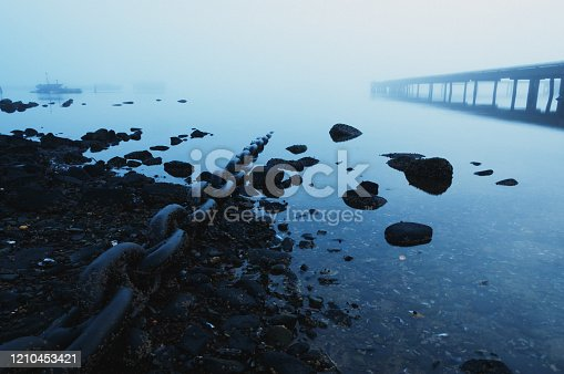 A heavy chain leads into a still inlet shrouded in heavy fog.