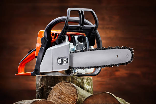 chainsaw and cut logs fire wood on brown wooden background. renewable resource of a energy. - chainsaw stock photos and pictures