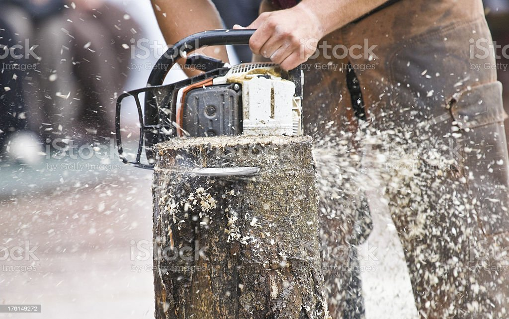Chainsaw cuts through log as chips fly royalty-free stock photo