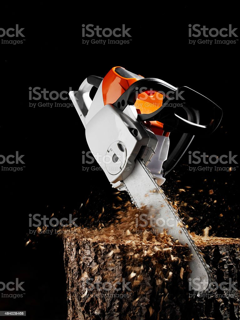 Chainsaw sawing by itself stock photo