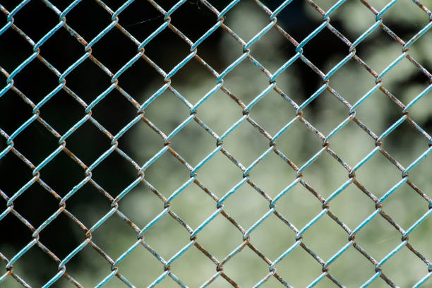 Chain-wire fence. Fence made of steel wire mesh. In places, the rusted wire mesh steel with shabby paint stock photo