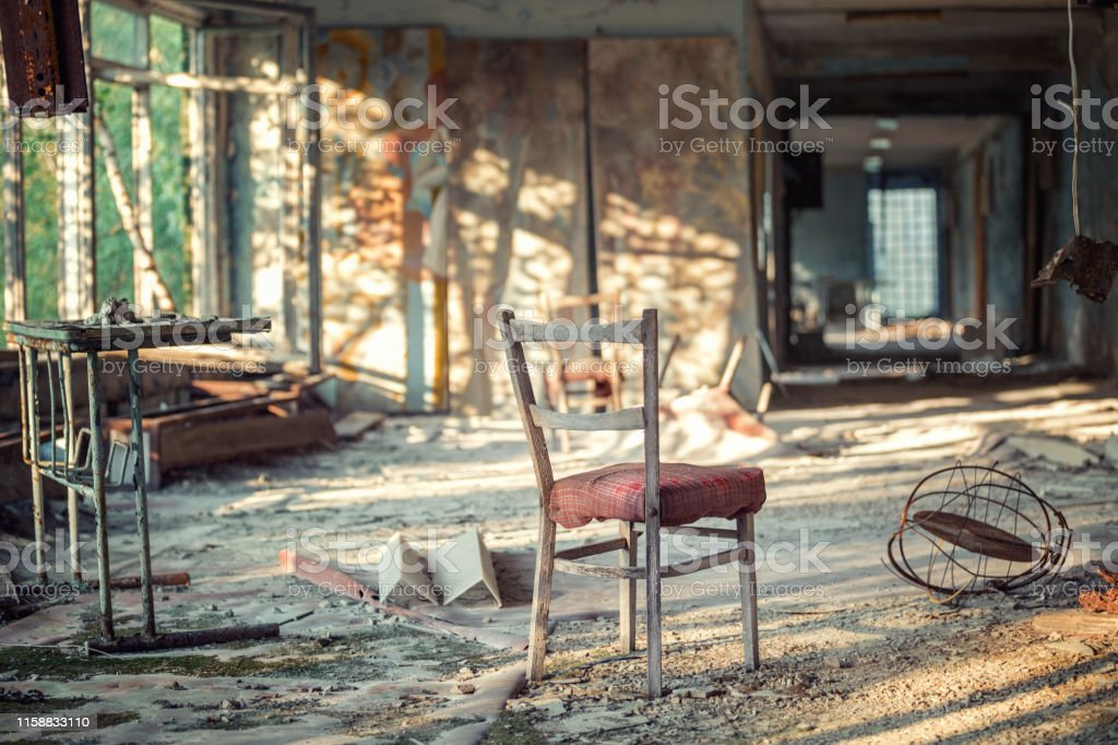 Chair and other broken furniture in the hall of abandoned school...