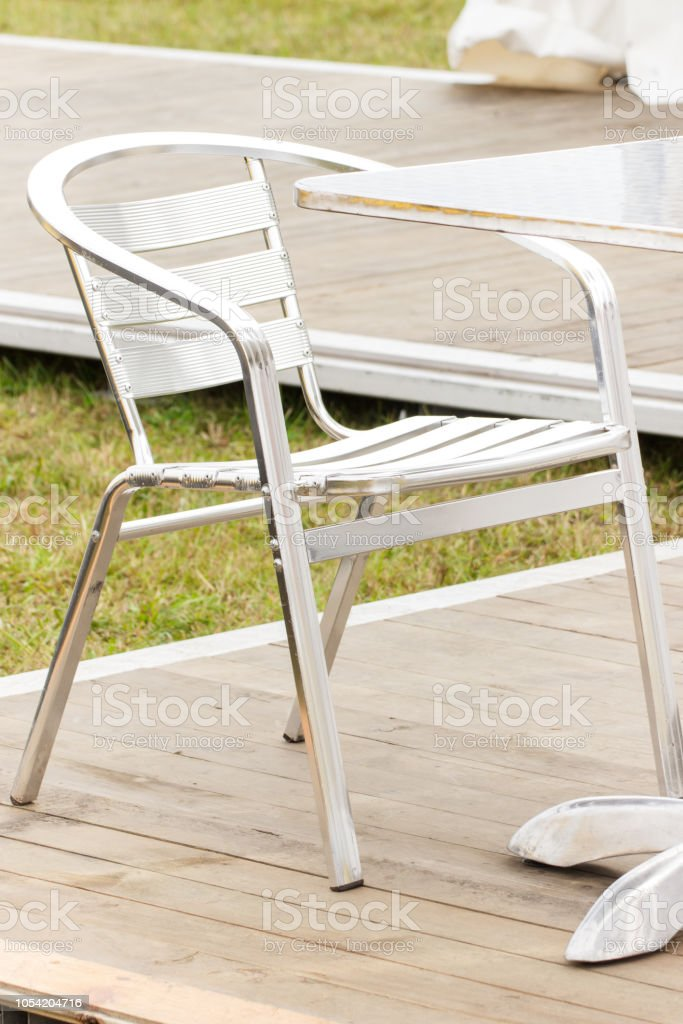 Metal silver chair and table on fresh air in outdoor restaurant or...