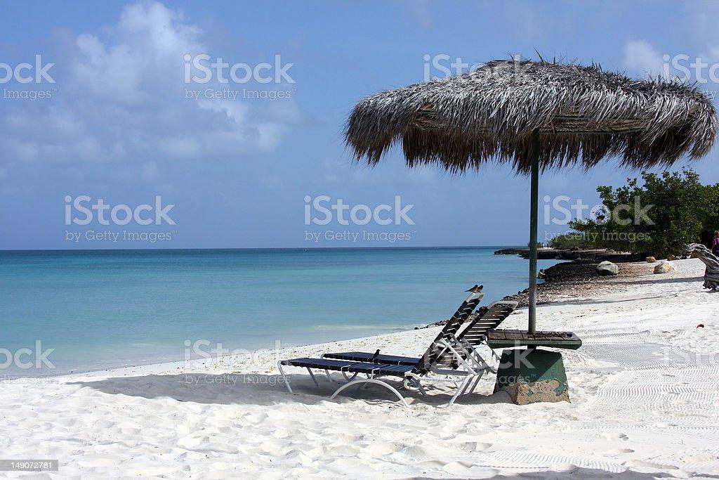 chair and umbrella on beach stock photo