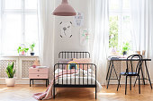 Chair at desk next to bed in pink and white girl's room interior with plants and windows. Real photo