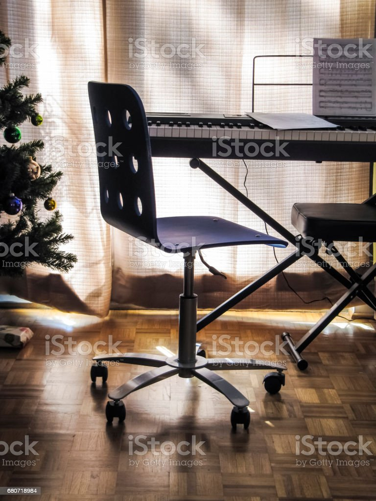 Chair by piano and Christmas tree during sunset with blinds stock photo