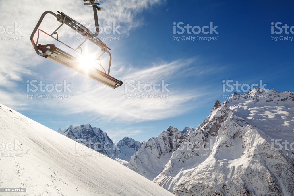 Chair lift on a mountainside on background of blue sky, snow-capped mountains and a bright winter sun stock photo