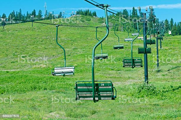Photo of Chair lifts idle in summer at ski area on mountain