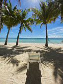 istock Chair on beach.Resort with sea.Shadows from palm leaves on sand.Hammock on tree 1215546860