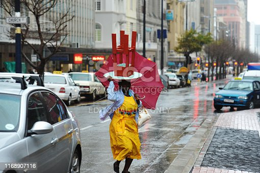 Cape Town, South Africa, 4 August 2011.  A woman walks down Adderly Street in the rain holding an umbrella with a stoel on her head.