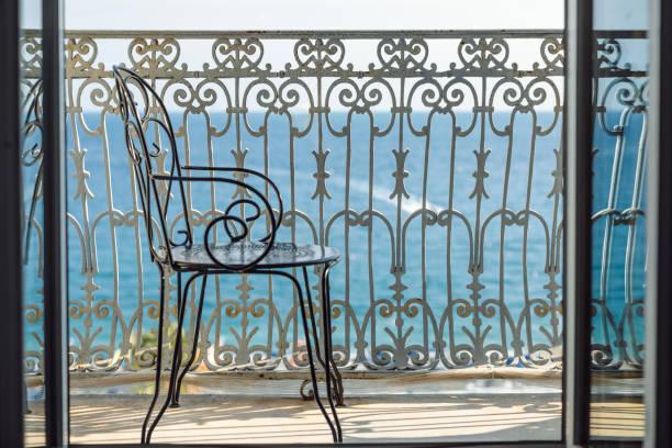 stuhl auf dem balkon - nizza sehenswürdigkeiten stock-fotos und bilder