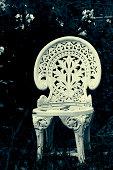 vintage white chair in bushy garden