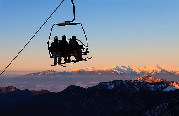 Chair ski lift with skiers at sunset stock photo