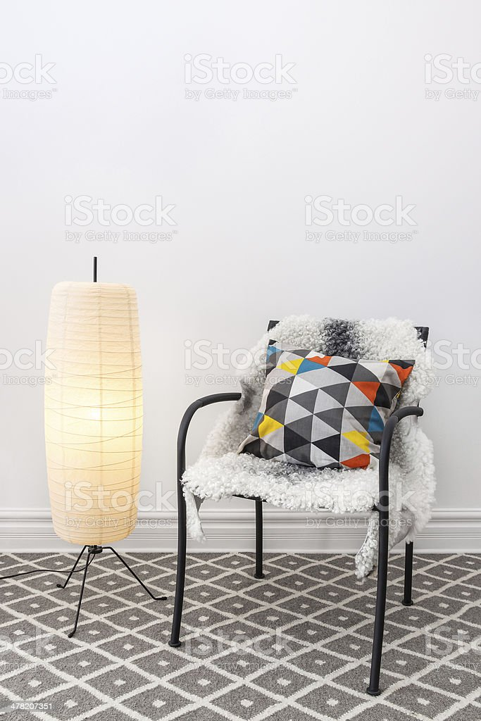 Chair with bright cushion and elegant floor lamp stock photo