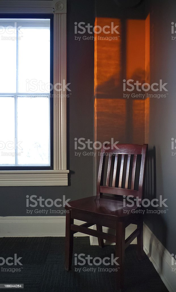 Chair with sunset window glow stock photo