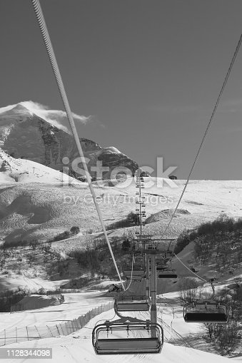 Chair-lift and ski slope in snowy mountains at sunny winter day. Caucasus Mountains. Mount Tetnuldi, Svaneti region of Georgia. Black and white toned landscape.