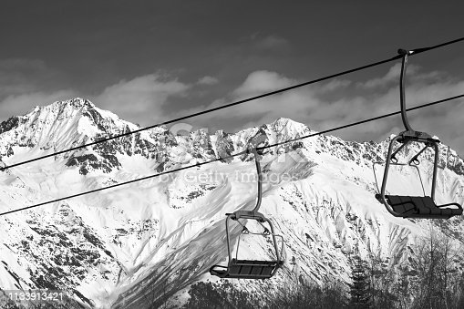 Chairlift on ski resort and snowy mountains at nice sunny day. Caucasus Mountains in winter. Hatsvali, Svaneti region of Georgia. Black and white toned landscape.