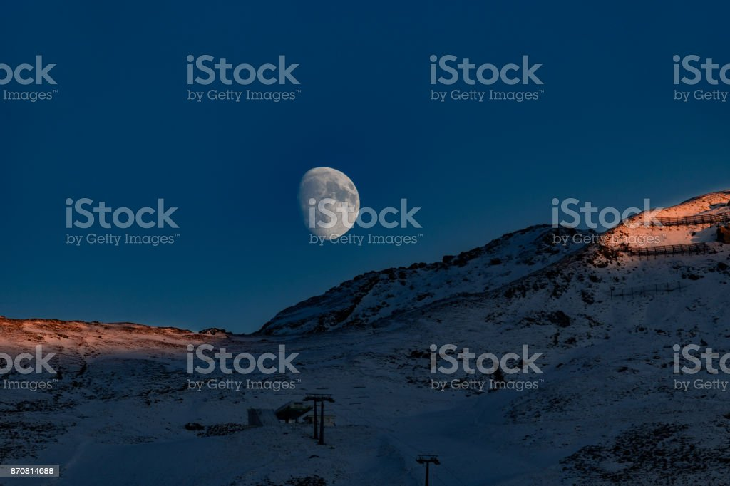 chairlift with alpenglow and moon stock photo