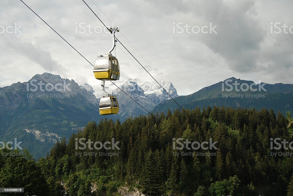 Chairlift with mountain peaks in background stock photo