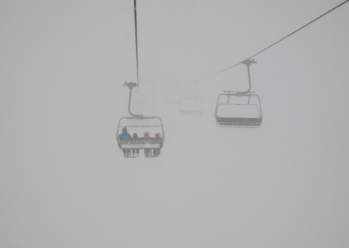 istock Chairlift with ski tourists disappers in dense fog 177834851