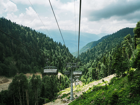 Chairlifts at mountains and forest background
