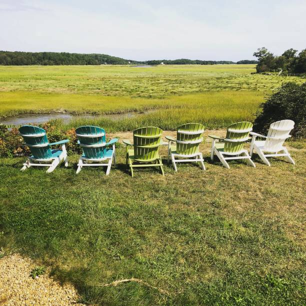 Chairs along a saltmarsh Colorful chairs set along a salt marsh in Gloucester, Mass. gloucester massachusetts stock pictures, royalty-free photos & images