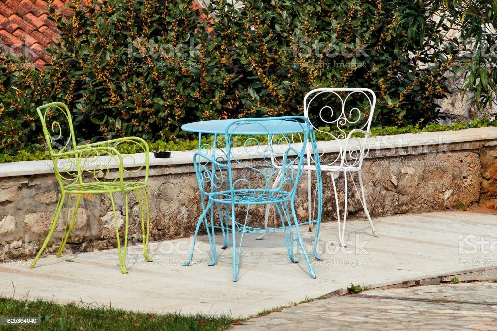 Cadeiras e uma mesa no jardim. Cadeiras de aço coloridas e uma pé de mesa em um belo jardim em dia de sol. Mobília do pátio. Um conjunto de três cadeiras coloridas e uma pequena mesa conjunto ao ar livre. - foto de acervo