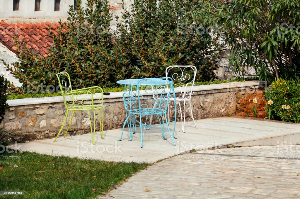 Chairs and a table in garden. Colorful steel chairs and a table standing in a beautiful garden at sunny day. Patio furniture. A set of three colored chairs and a small table set outdoor. stock photo