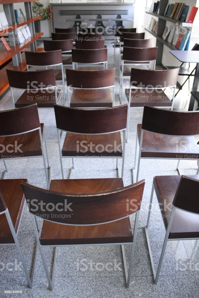 Several wooden chairs in row, indoors and outdoors of a book cafe...