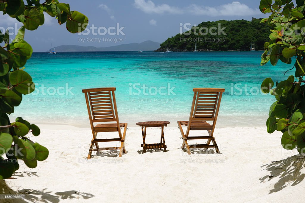 chairs and table on a beach in the Caribbean stock photo
