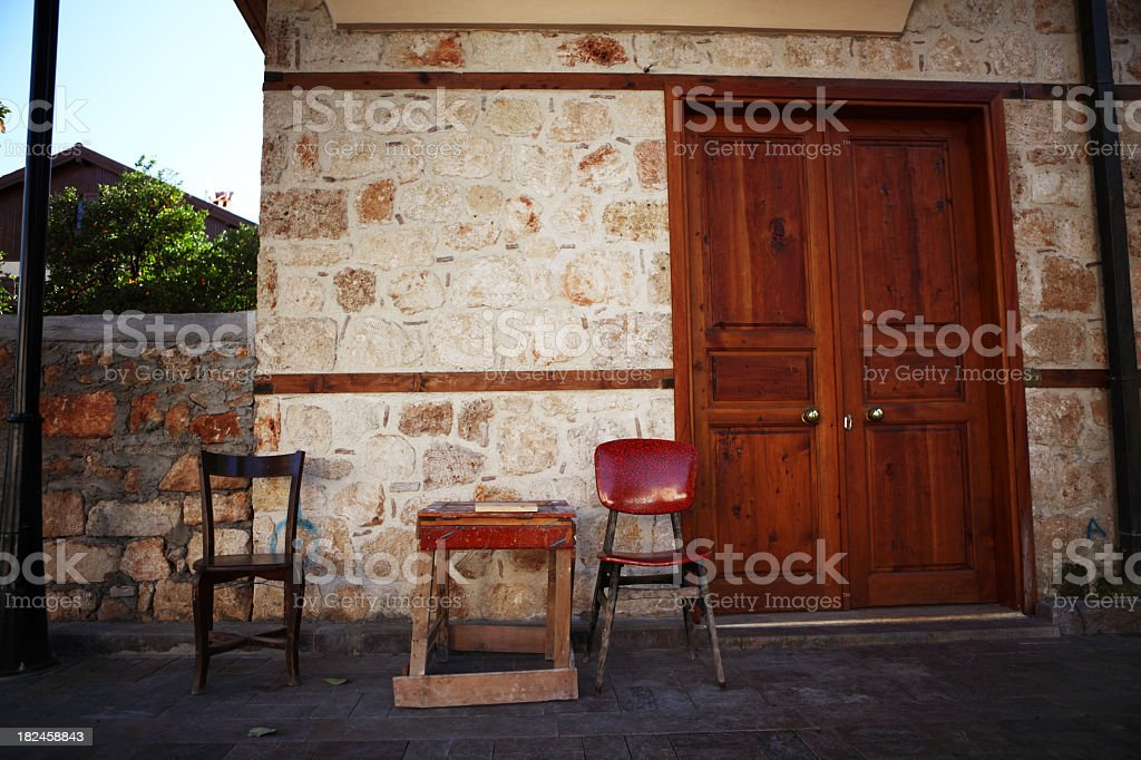 Chairs and table outside a stone house royalty-free stock photo