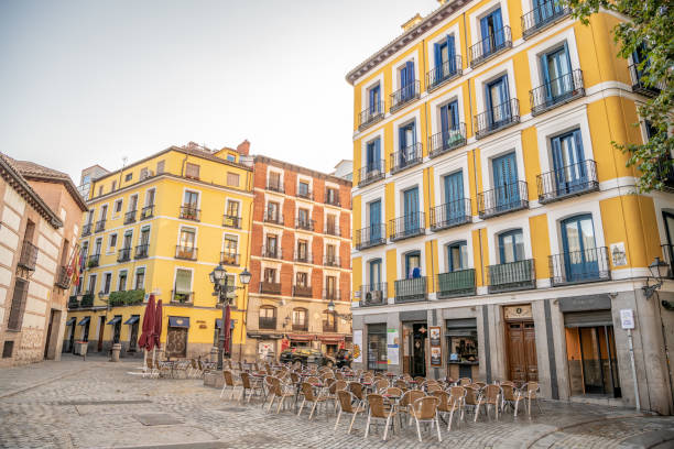 Chairs and tables set out on a plaza in the La Latina neighborhood in Madrid. stock photo