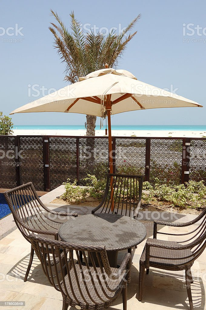 Chairs and umbrella near swimming pool by a beach stock photo