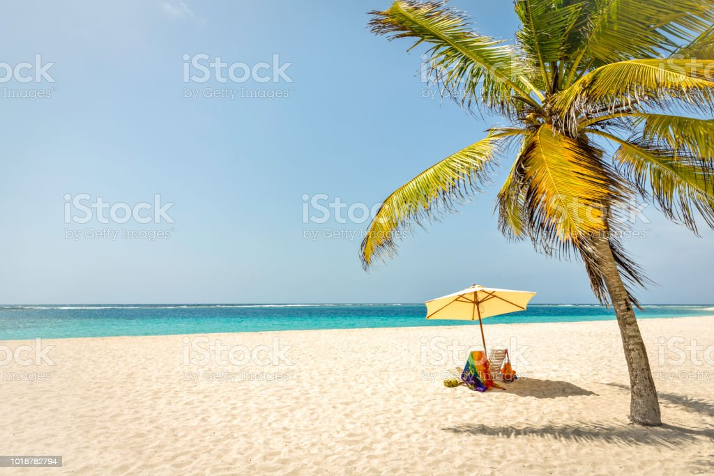 Chairs and umbrella on a tropical white sand island beach in the Caribbean sea stock photo